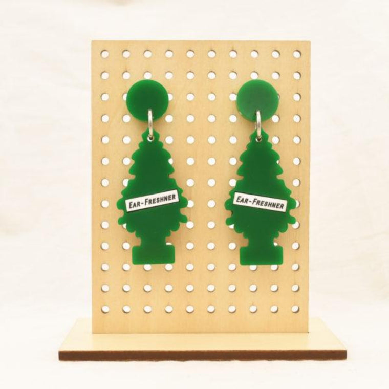 Image featuring a tanned wood stand holding two graphically illustrated green tree air fresheners with the text ear-freshner on the front