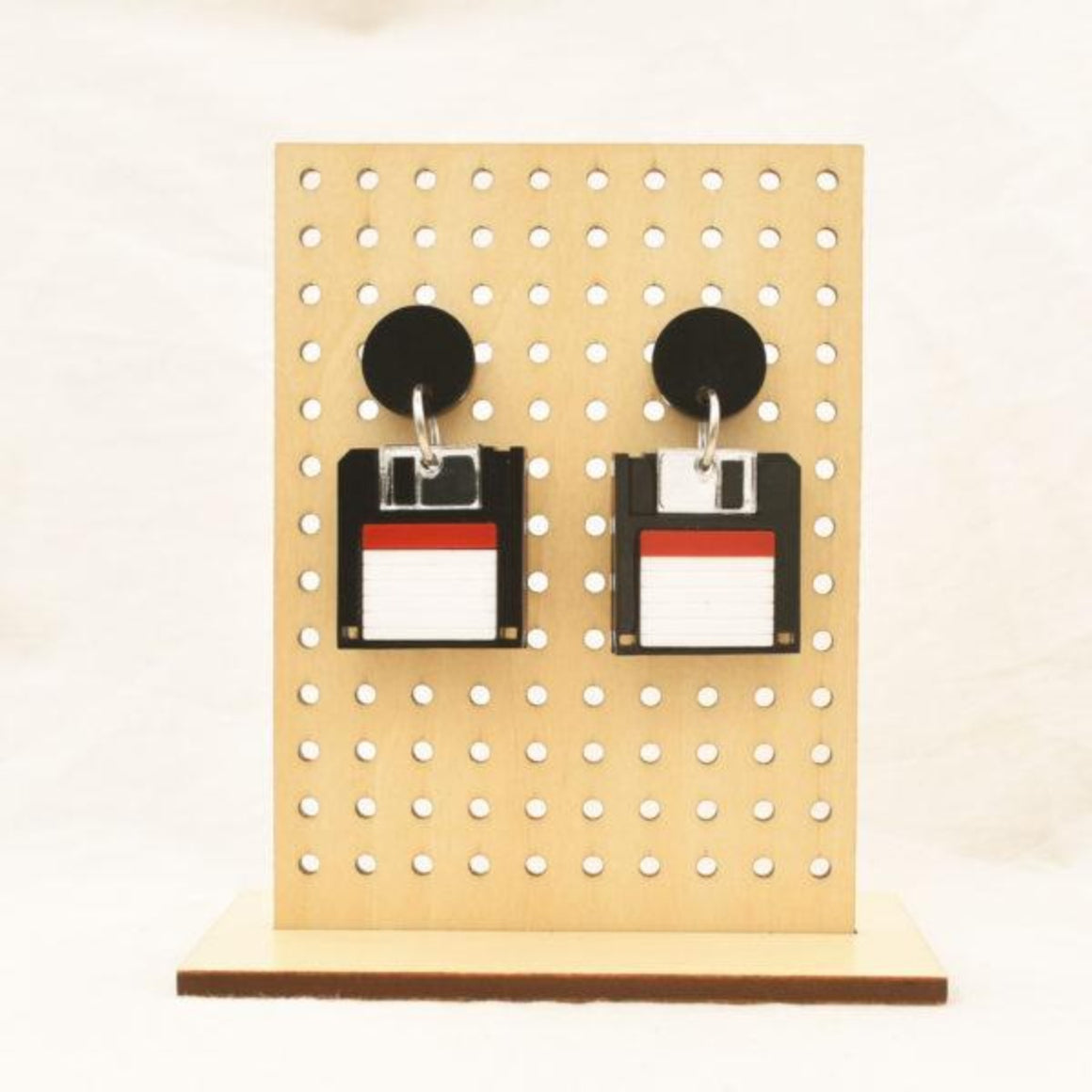 Image featuring a tanned wood stand holding two graphically illustrated earrings with floppy disc in a black, red, white colours