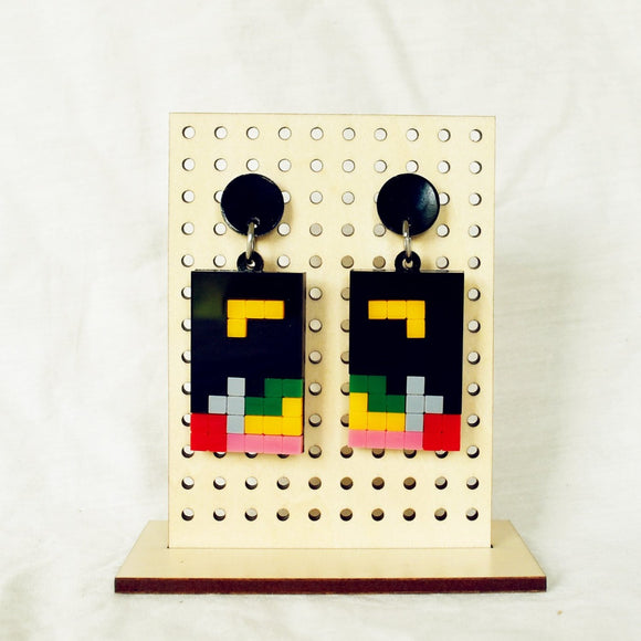 Image featuring a tanned wood stand holding two graphically illustrated earrings both a game of tetris which includes the colours black, yellow, green, grey, pink and red