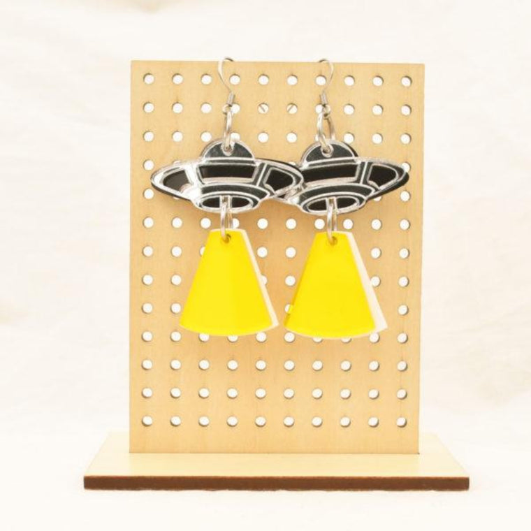 Image featuring a tanned wood stand holding two graphically illustrated earrings both with a UFO and including a yellow ray of light underneath them