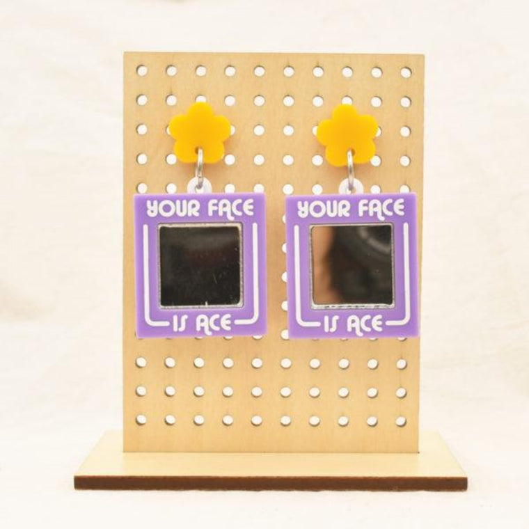 Image featuring a tanned wood stand holding two graphically illustrated earrings both with a purple square, with a mirror in the center with the text Your Face is Ace surrounding the mirror with a yellow flower above it