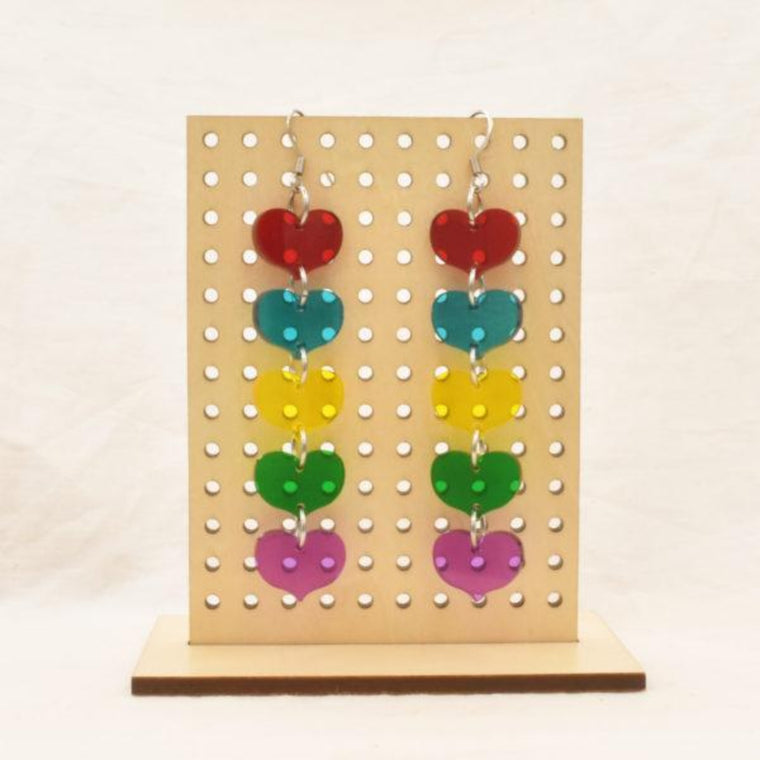 Image featuring a tanned wood stand holding two graphically illustrated earrings both featuring a string of Perspex hearts in red, blue, yellow, green and purple colours