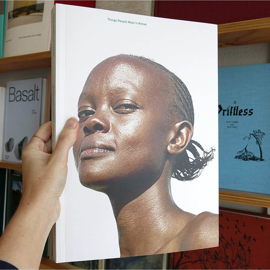 A large book cover featuring a photographic portrait of a smiling Kenyan woman on a white background.
