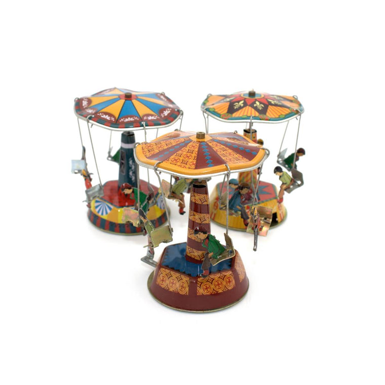 Three tin toy carousels in primary colours. Each carousel has 6 seats suspended from the canopy, with small figures seated on each
