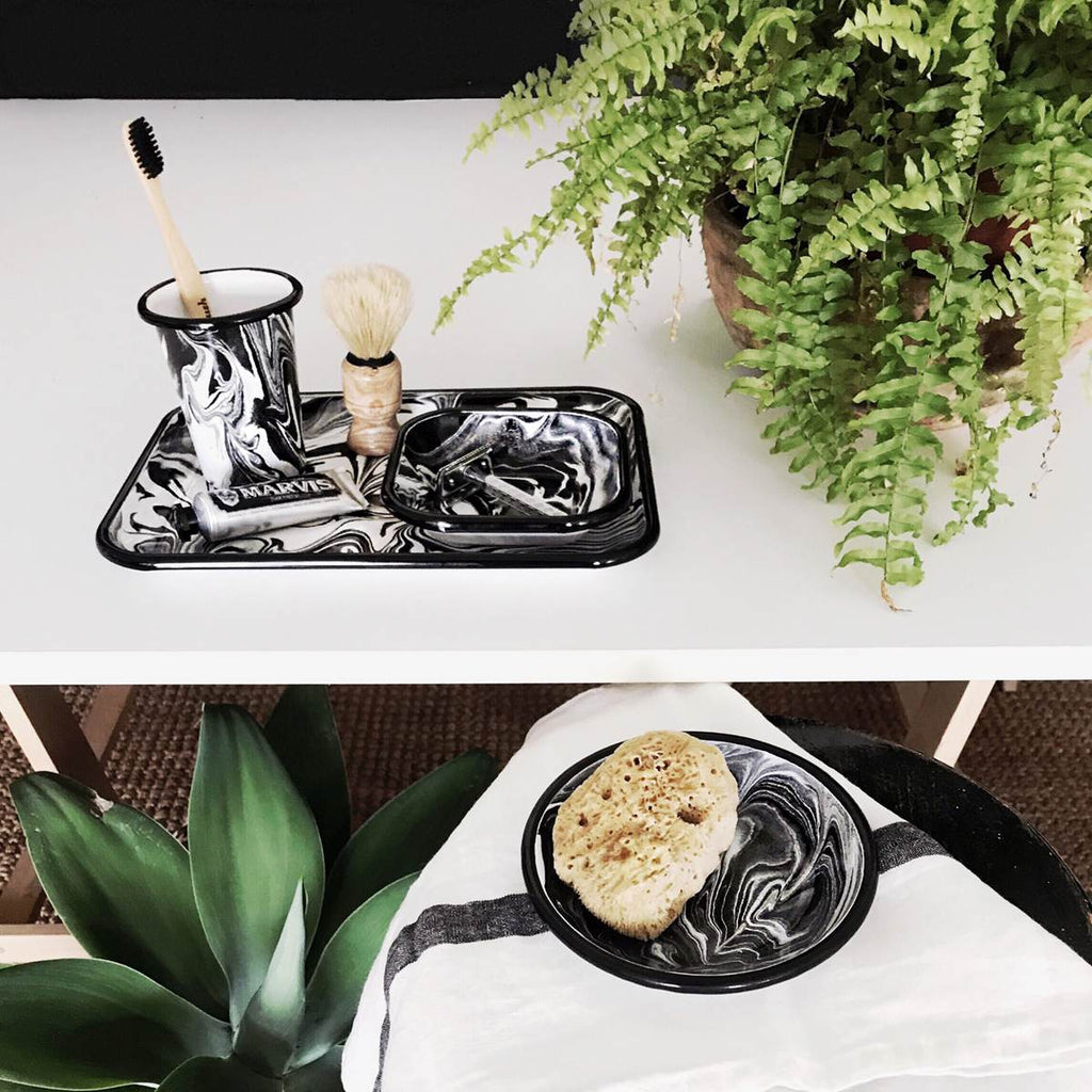An enamel tumbler and plate set with beautiful marbled enamel in a range of contrasting tones of black and white. Shown in use as a shaving kit. featuring shaving cream, brush, sponge and toothbrush as props.