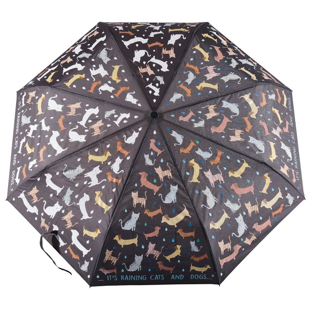 A black umbrella covered in a print of dogs and cats.. The image shows how when water hits the umbrella the dogs and cats transform from white to fully coloured.