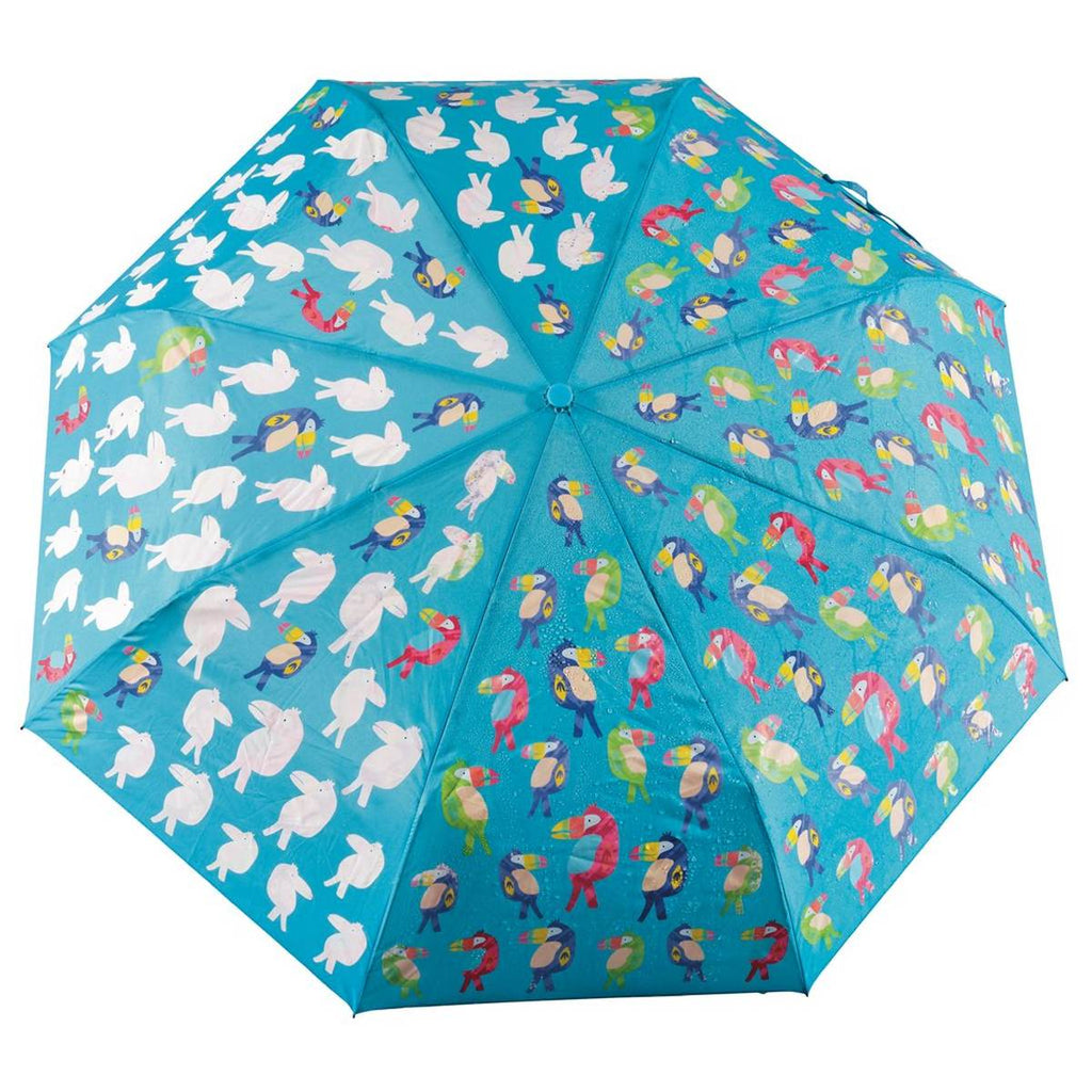 A blue umbrella covered in a brightly coloured print of toucans. The image shows how when water hits the umbrella the toucans transform from white to fully coloured.