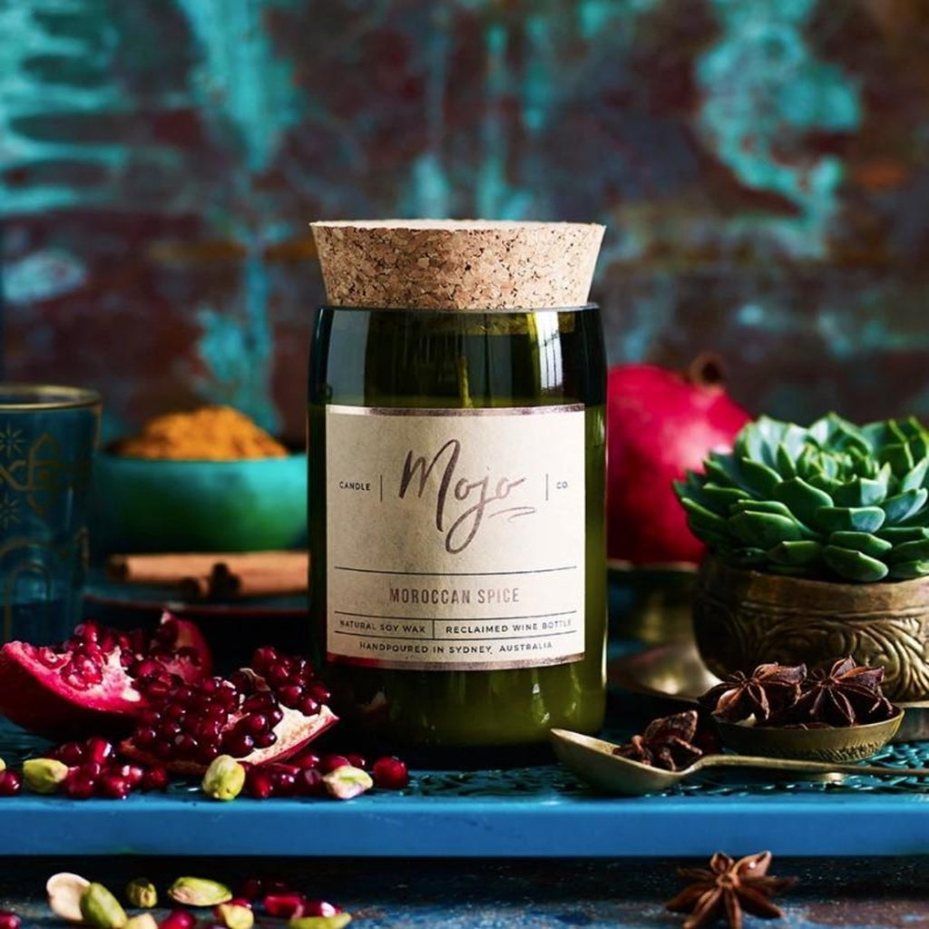Candle featured in a recycled green wine bottle centered around a moroccan themed background which includes cactus, pomegranates, moroccan spices and a blue coloured feature background