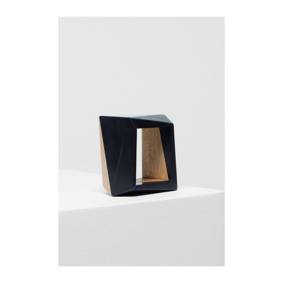 Image featuring a geometric bangle with a black resin face facing the camera and with bits of wood that can be seen at the back