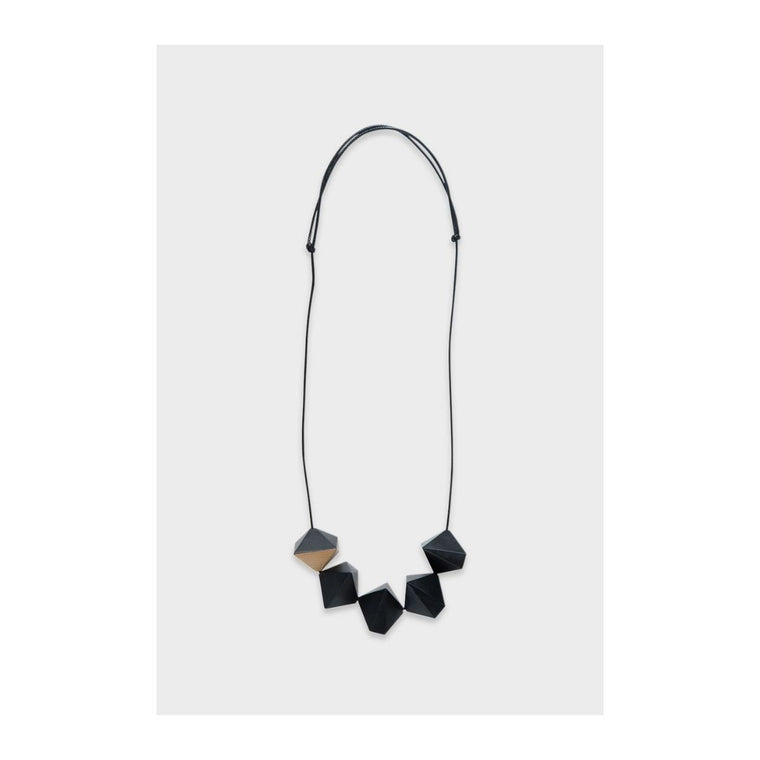 Image featuring a necklace in the center, on the bottom of the necklace features five black resin diamond shapes which also include a wooden texture