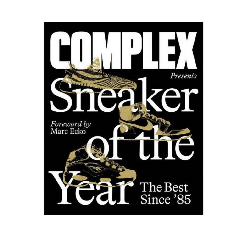 Photograph of a black book cover with white bold text which states Complex presents Sneaker of the Year -The Best since '85, Foreword by Marc Ecko which also includes gold foil images of various sneakers