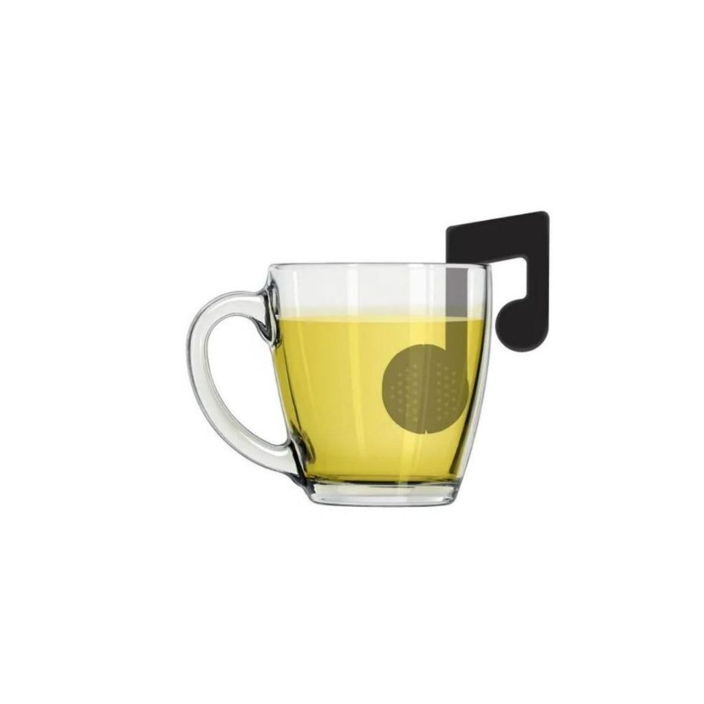 Image featuring a glass cup in the center which on the left hand side is holding the music note tea infuser inside it