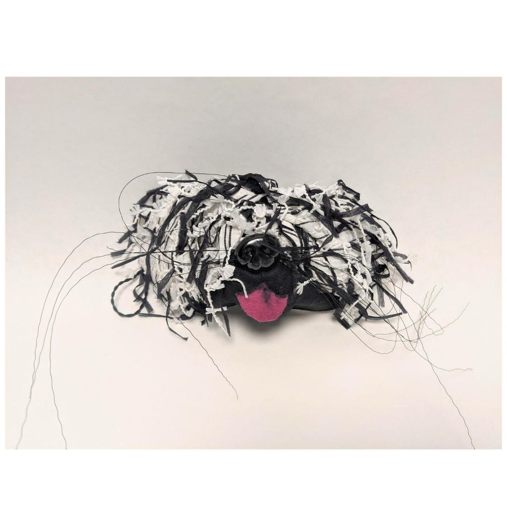 Mask featuring shaggy black and white fabric made to look like fur including a pink fabric tongue, black plastic dog nose and wire whiskers