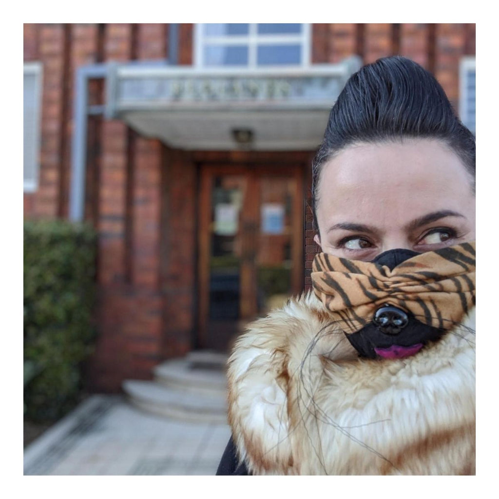 Photograph of a woman featured in front of a building wearing a fluffy coat with a tiger striped mask on which includes wire whiskers, pink fabric tongue and a black plastic dog nose