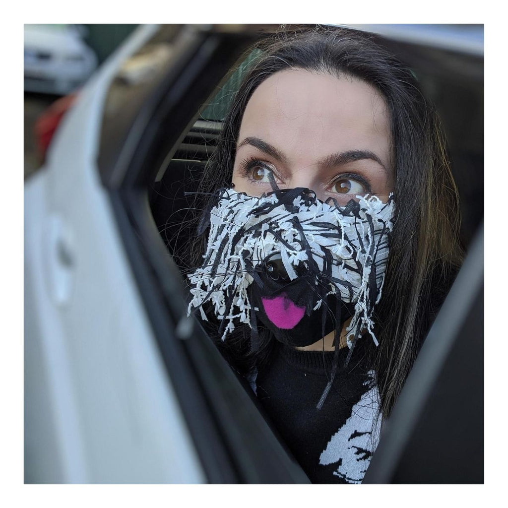 Photograph of a woman featured in a car wearing a mask with black and white fabric made to look like fur with a pink fabric tongue and a black plastic dog nose