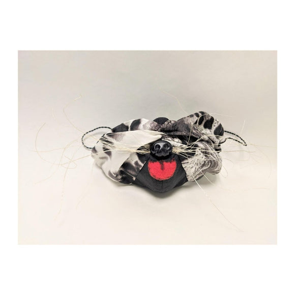 Mask featuring snow leopard print and black fabric which includes wire whiskers, pink fabric made to look like a tongue and black plastic dog nose