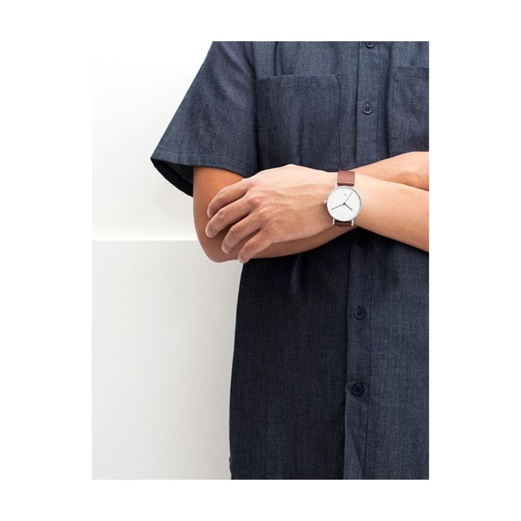 Image of a model wearing a denim shirt dress who has their arms crossed and wearing the Stock S004b Watch on one of her arms