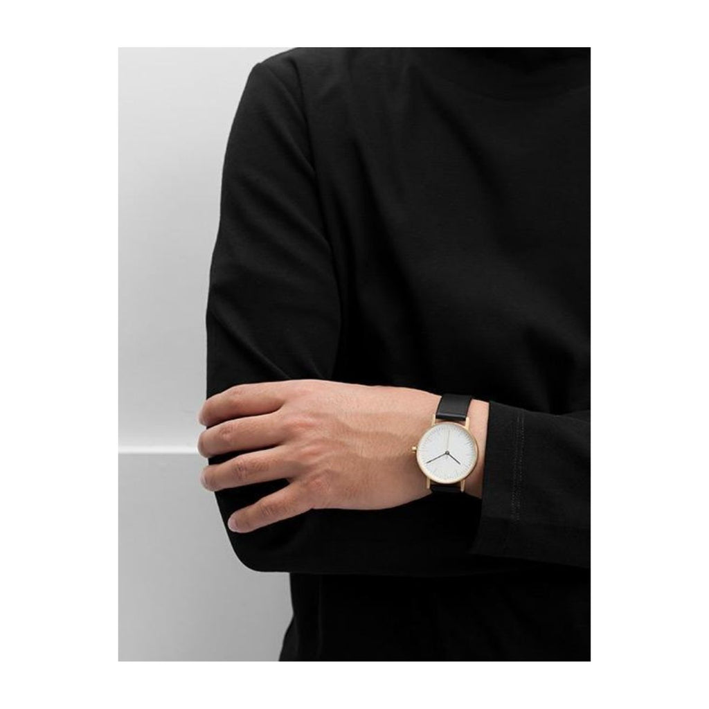 Image with a model wearing a black shirt with arm placed across their chest featuring a watch on the arm