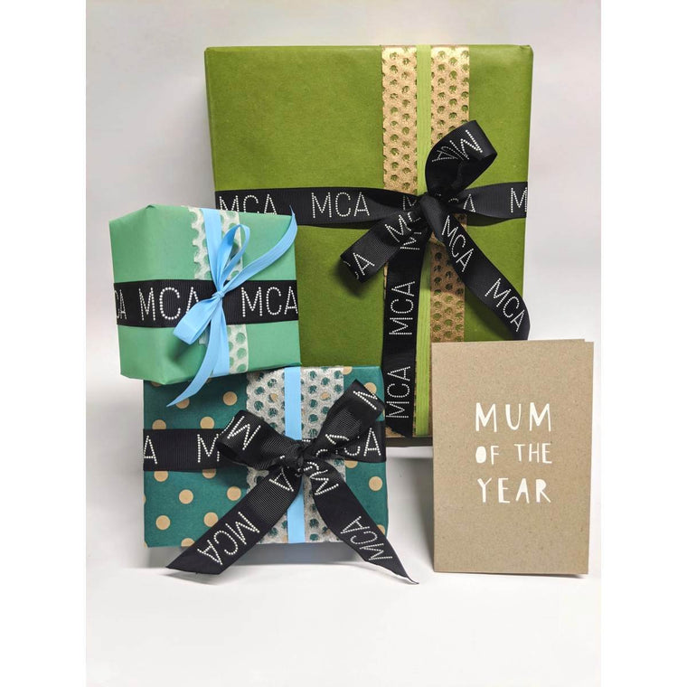Three Gifts beautifully wrapped in a range of Green and Blue toned Paper and Ribbons. Each are finished with a MCA grosgrain ribbon. A Mothers Day Greeting card sits in front