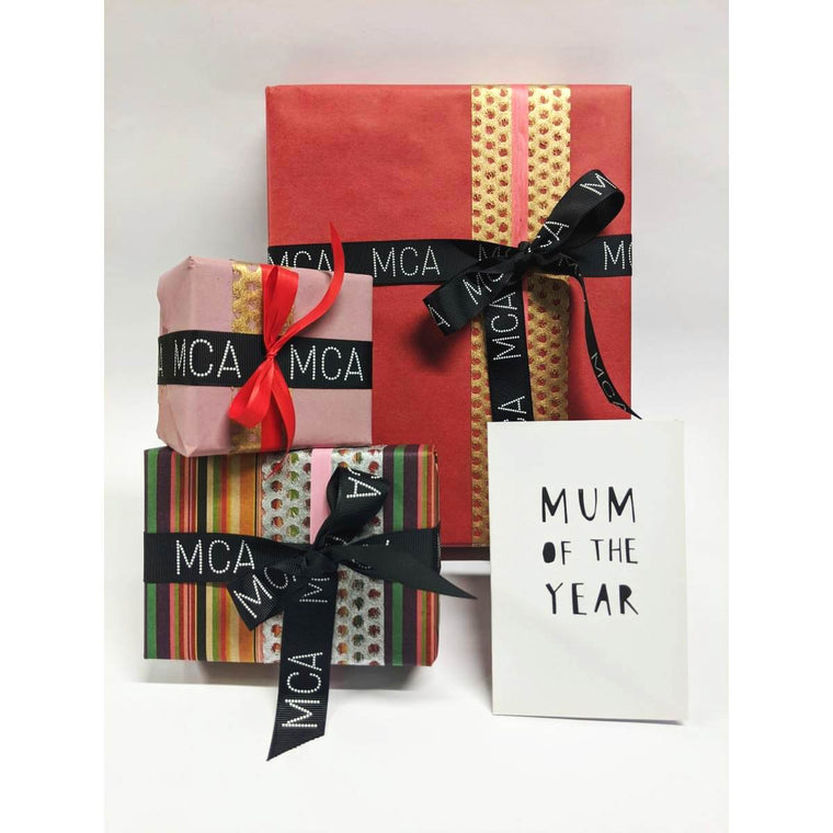 Three Gifts beautifully wrapped in a range of Red and Pink toned Paper and Ribbons. Each are finished with a MCA grosgrain ribbon. A Mothers Day Greeting card sits in front