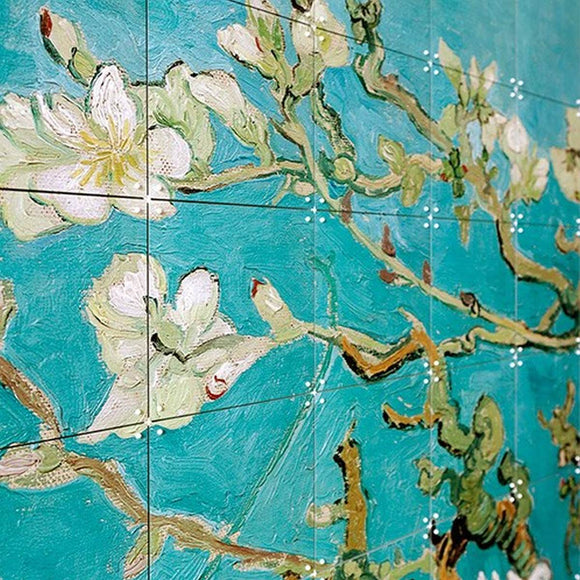 A wall hanging composed of multiple squares, linked together by connectors to form a larger image. This image is Almond Blosson by Vincent Van Gogh. A painting of an almond blossom set on a vibrant light blue background.
