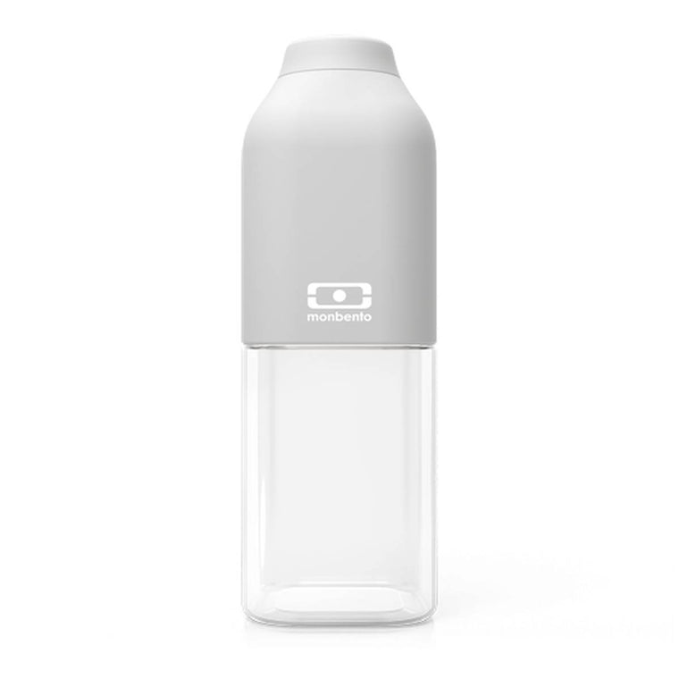 A Monbento Water bottle composed of clear tritan plastic and matte light grey silicon top.