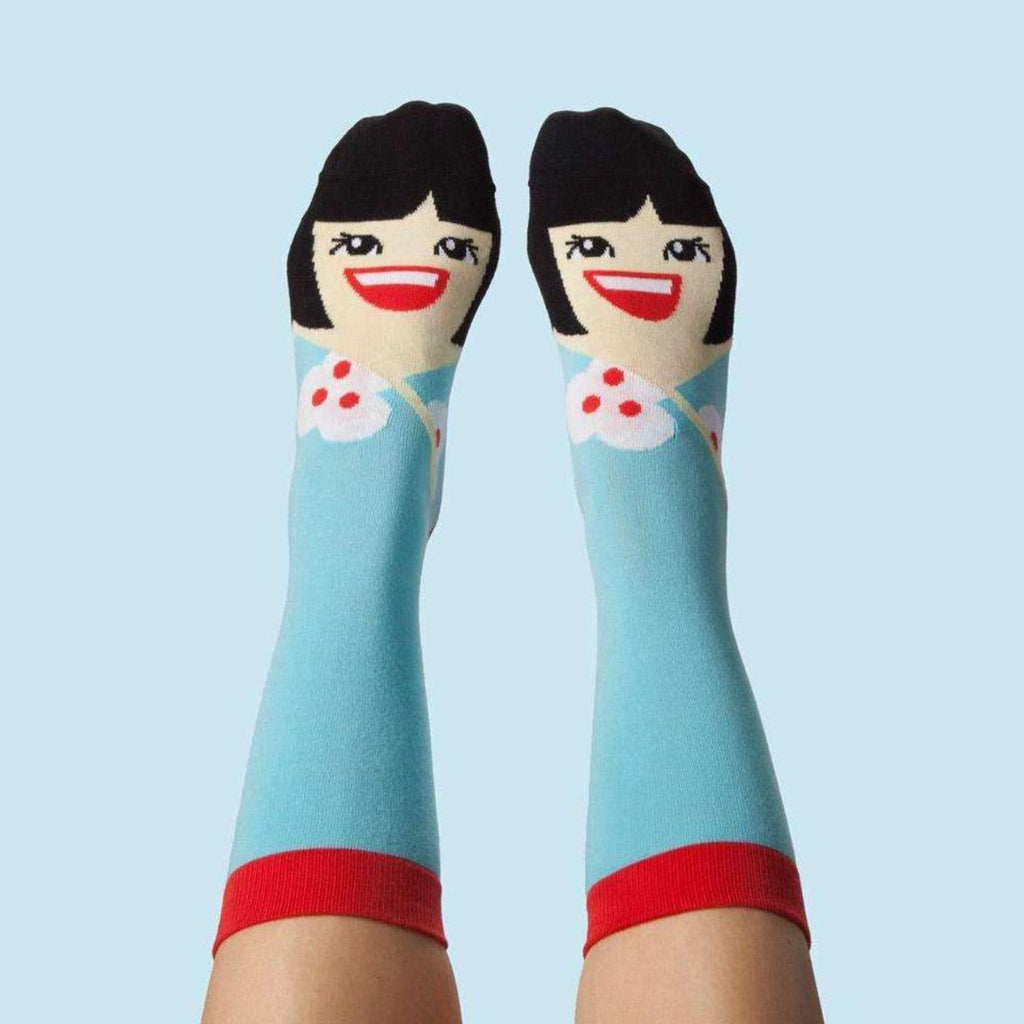 Image featuring a pair of feet that are wearing a pair of graphic illustrated socks of Yoko Ono