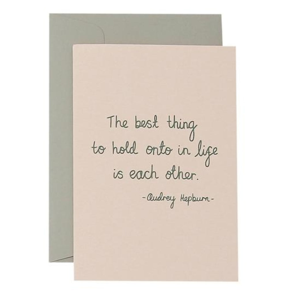 Blush Greeting Card with olive text saying the best thing to hold onto in life is each other. - Audrey Hepburn