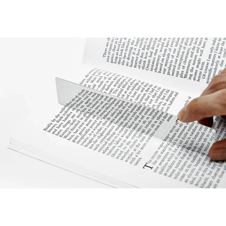 A silver minimalist and highly reflective bookmark. Shown in a book, producing a mirror image of the text on the page.