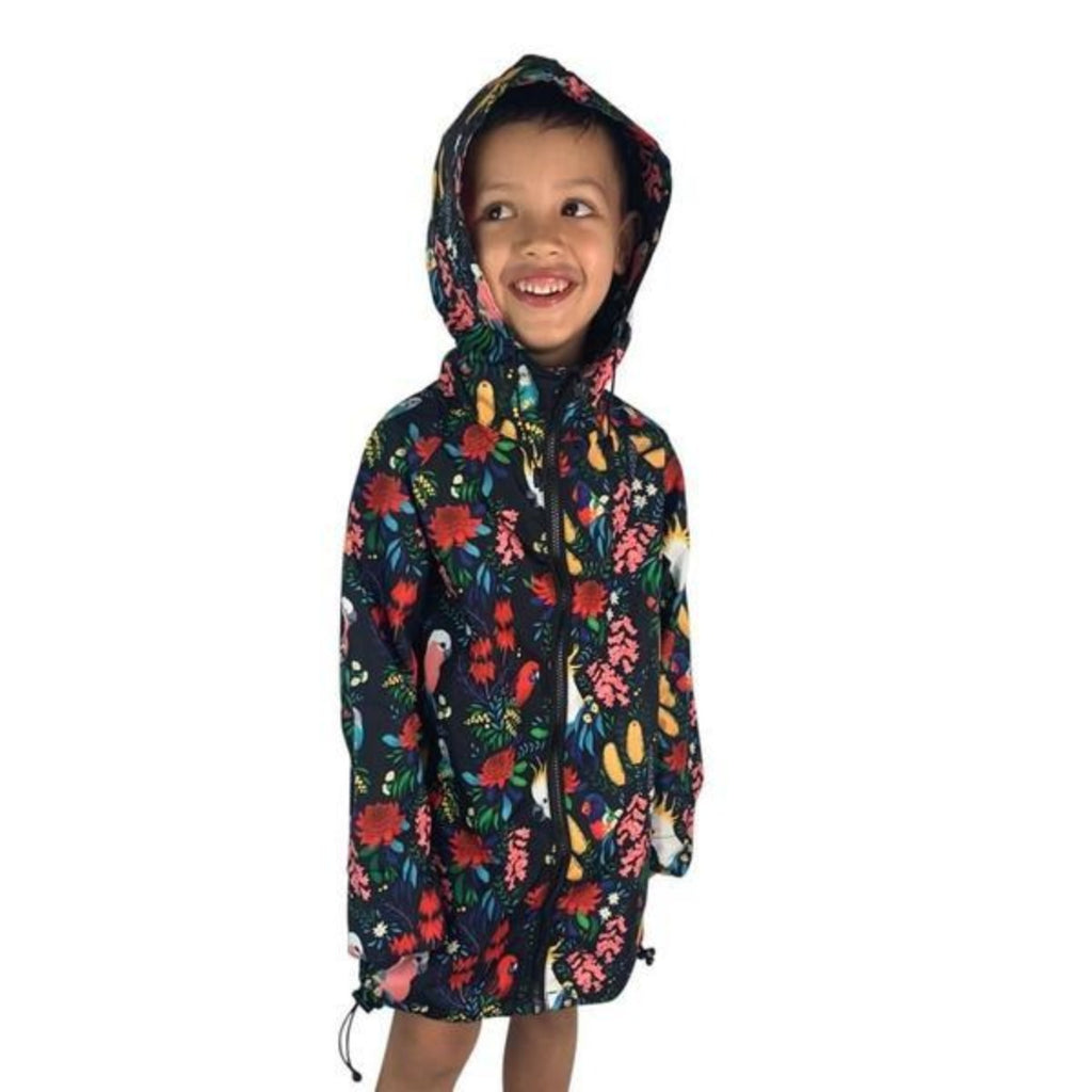 Child wearing a raincoat which features Australian florals such as Banksia, wattles and the sturt desert pea as well as Australian birds including Cockatoos, Rosellas and Rainbow Lorikeet