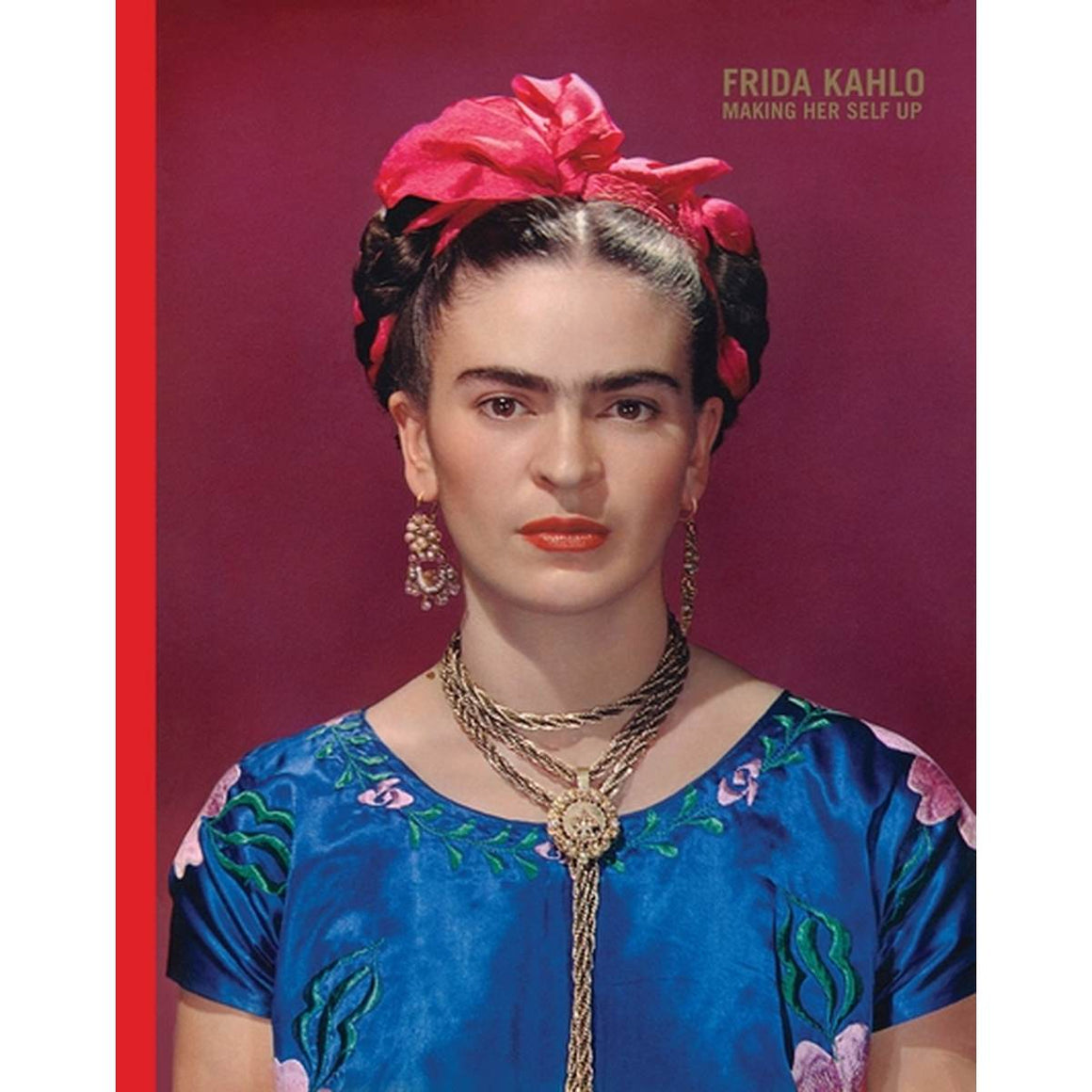 A book cover with a cover vibrantly coloured photo of artist Frida Kahlo on a maroon background