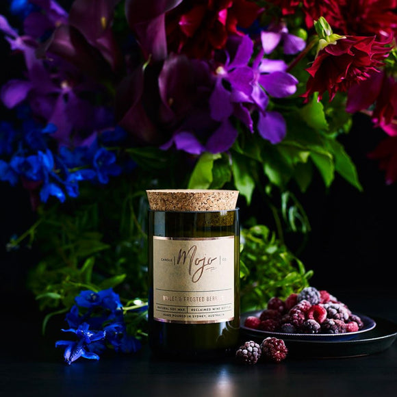 A Candle contained in a reclaimed wine bottle with a cork topper. It is photographed laying flat on a white surface surrounded by flowers, assorted berries, leaves and cinnamon quills