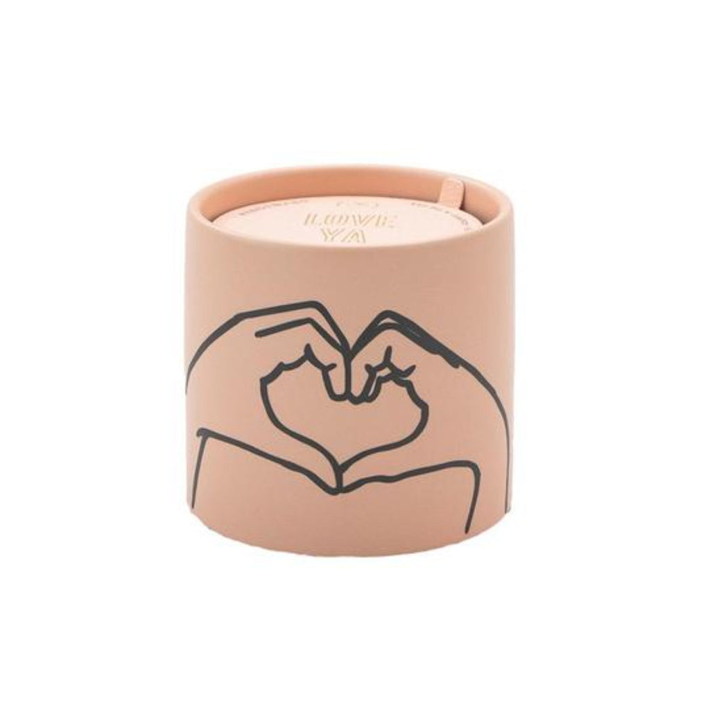 Image featuring a pastel pink ceramic candle which includes in the middle a graphic illustration two hands which have been shaped to look like a love heart