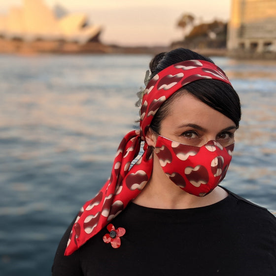 "A beautiful woman stands in front of a blurred Sydney Harbour and Opera House background. She wears coordinating Silk Head scarf and face mask bearing the work "" Double Negative"" by Cornelia Parker in Red and white. She wears a black top and an enamelled poppy brooch"