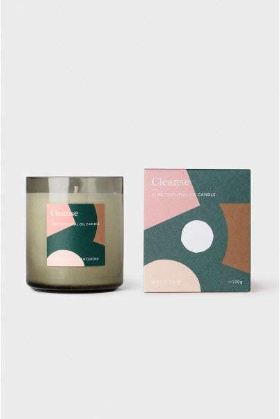 Candle Sat next to box packing featuring the words Cleanse on top of a geometric pattern print