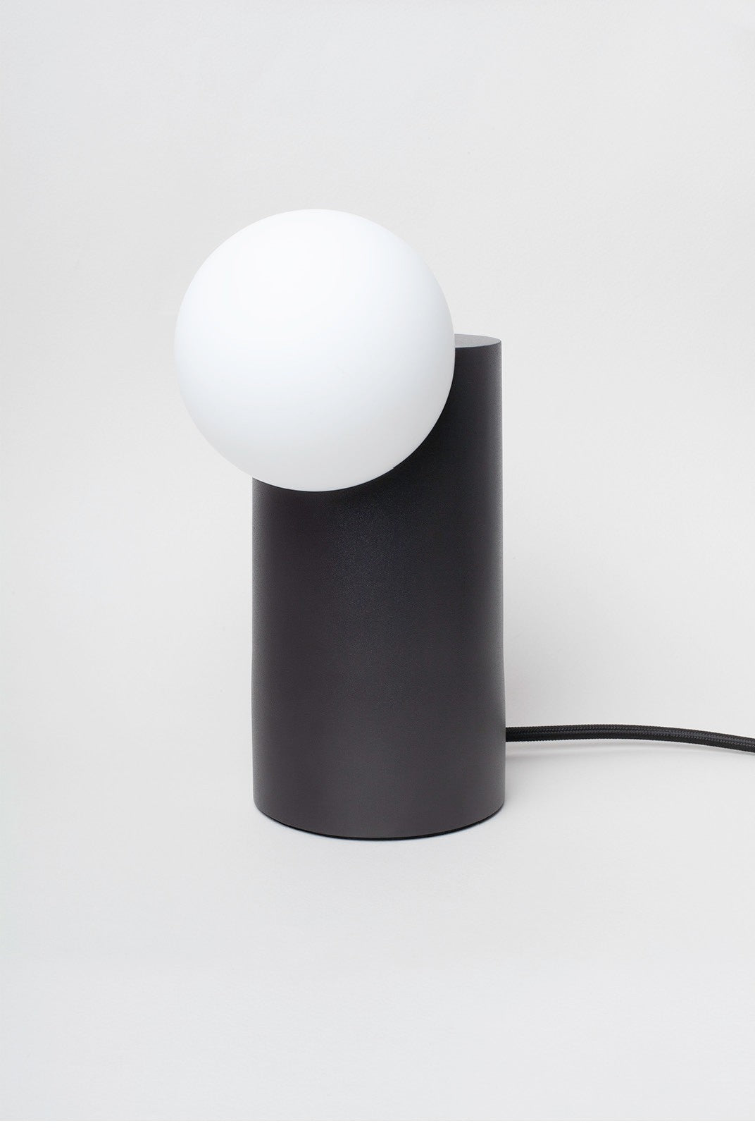 Lamp featuring a black cylinder with a circular globe