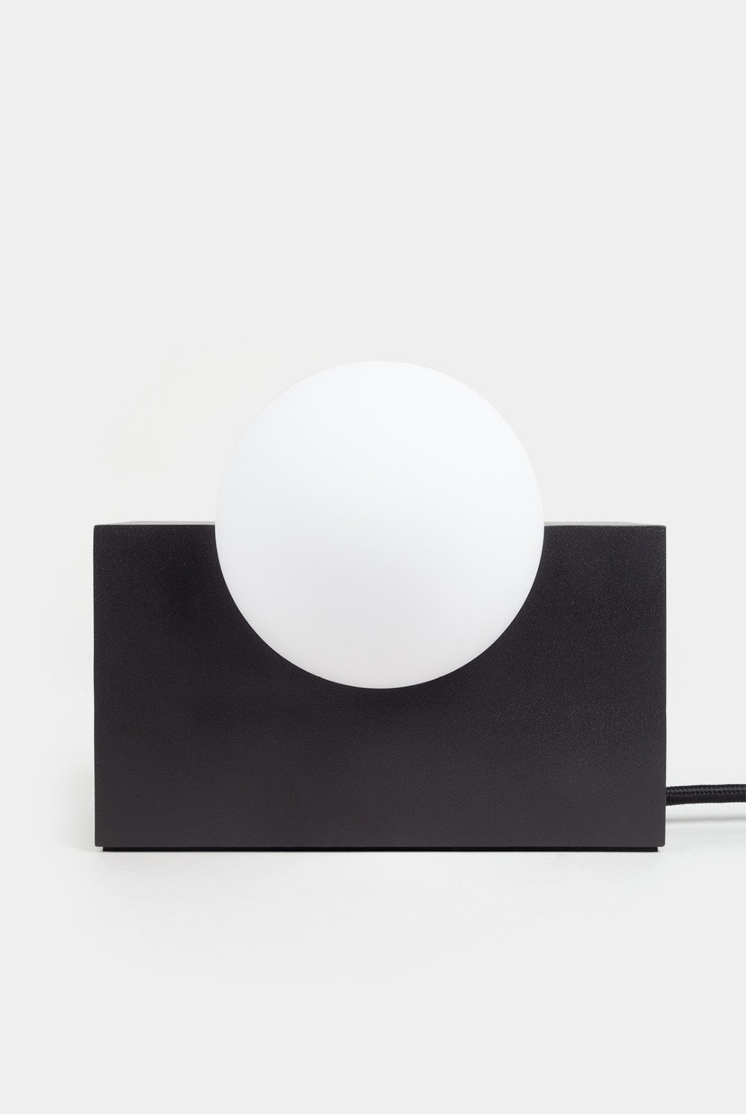 Lamp featuring a black rectangular with a circular globe