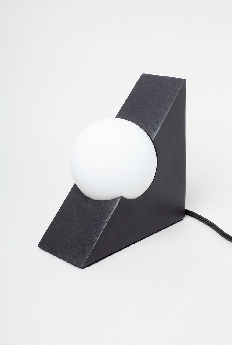 Lamp featuring a black triangle with a circular globe