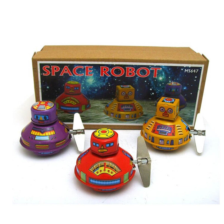 "A set of three small UFO shaped robot tin toys in red, purple and yellow. Shown in front of gift box featuring an image of the toys in space, and the text ""SPACE ROBOT"""