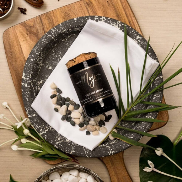 A Candle contained in a reclaimed beer bottle with a cork topper. It is photographed laying flat on a black and white stonewear plate- on a wooden chopping board surrounded by leaves and flowers.
