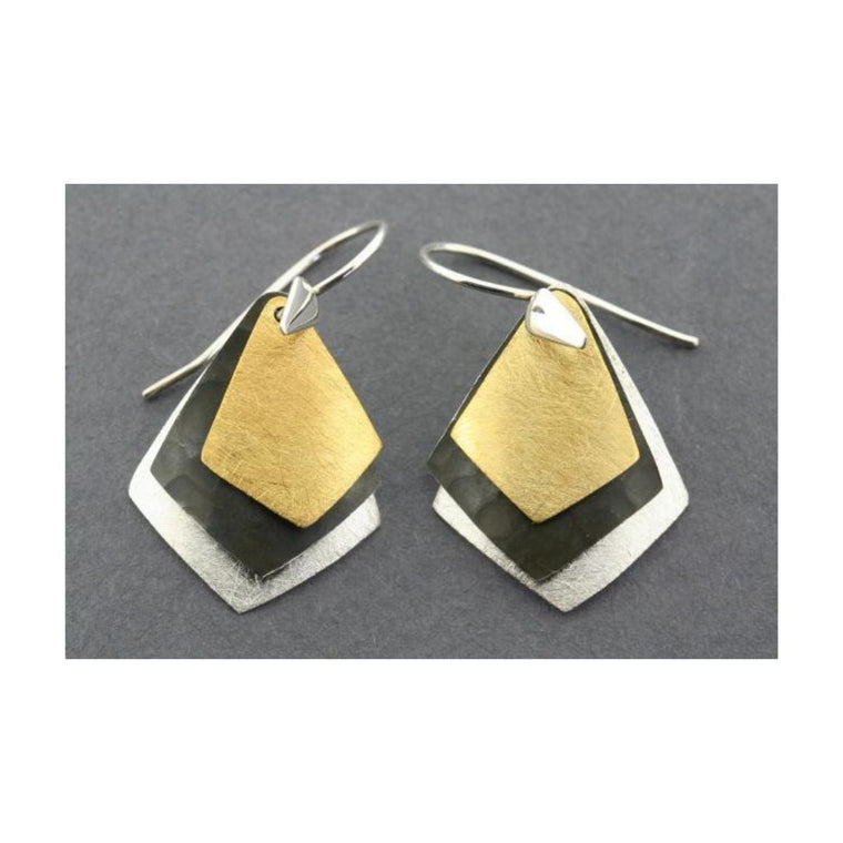 A pair of silver, gold and oxidized layered diamond earrings on a grey background