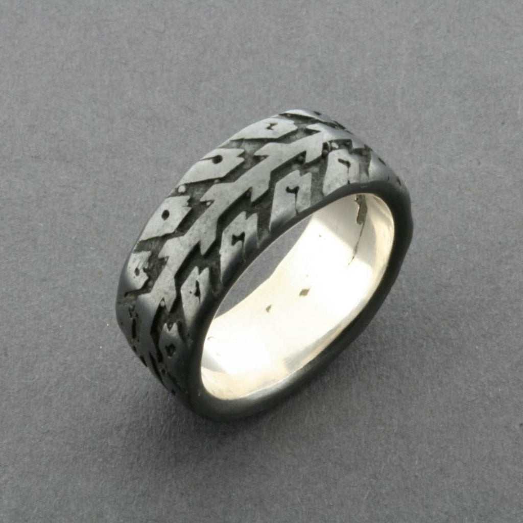 A Silver Band Style Ring, featuring a tire tread print etched into its surface
