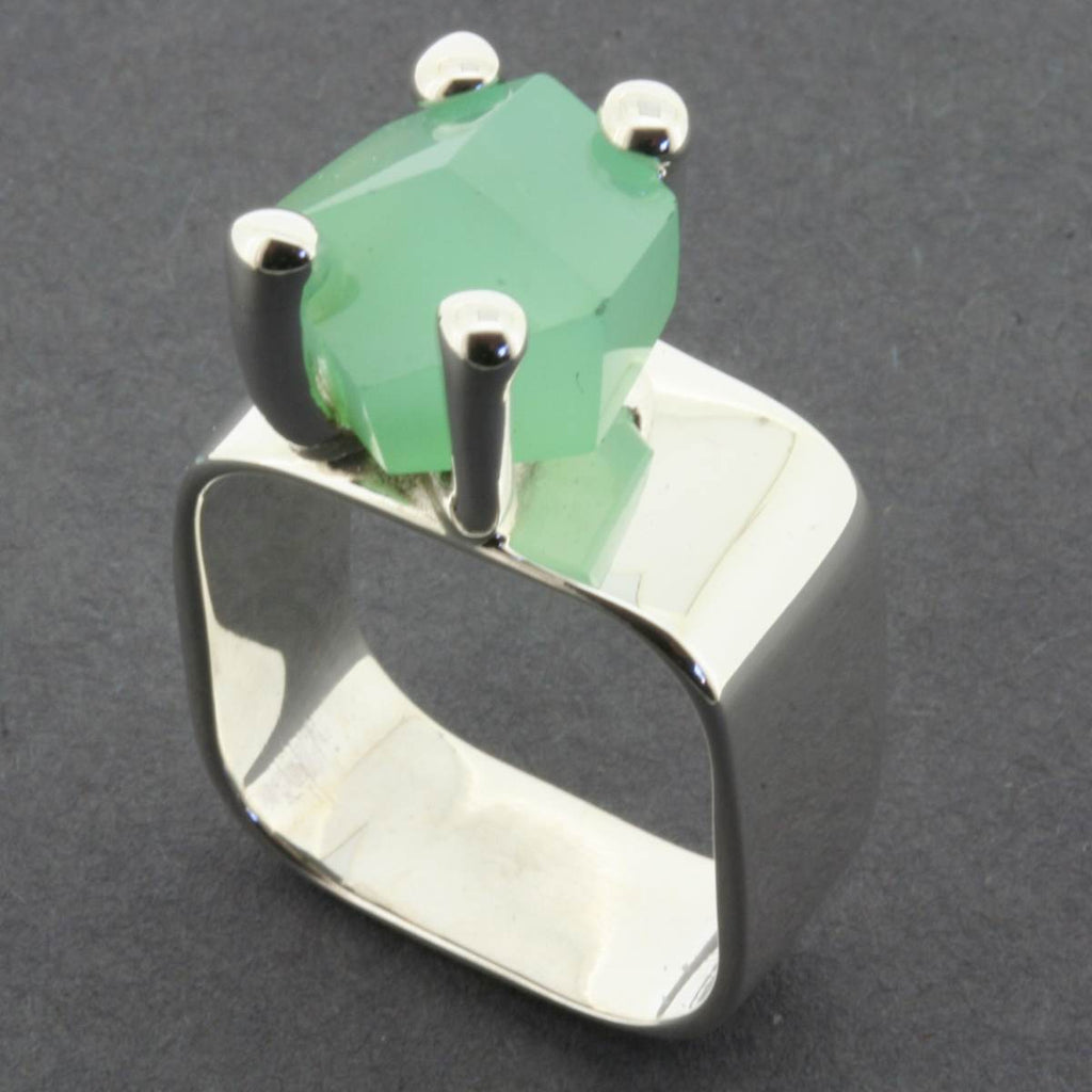 A silver band style ring, featuring a claw set rough cut Chrysoprase stone. The stone is a pastel green and the setting is slightly off centre.