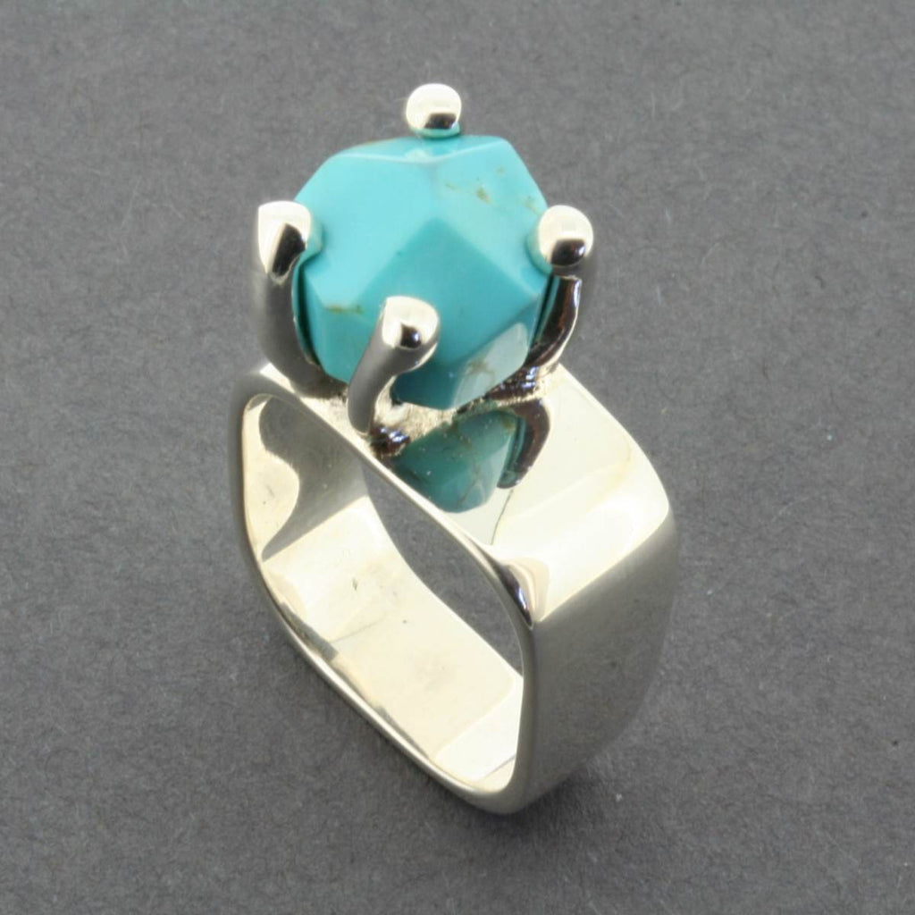 A silver band style ring, featuring a claw set rough cut Turquoise stone. The stone is a light blue and the setting is slightly off centre.