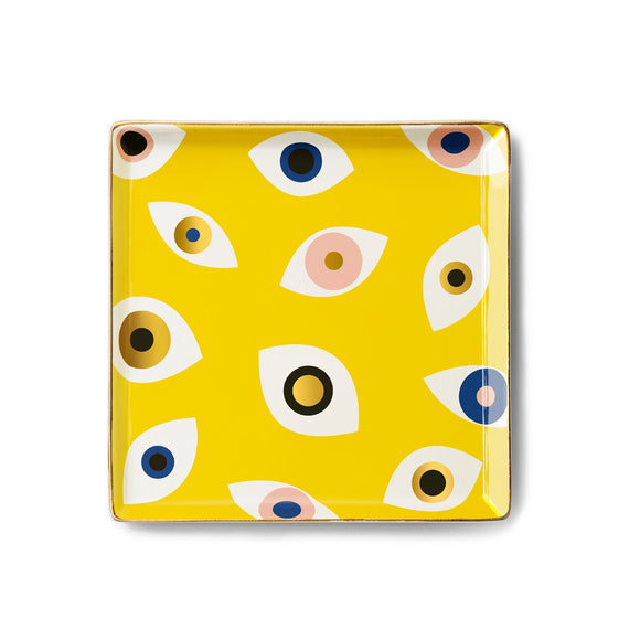A yellow square ceramic tray with eye motifs in white, gold, black , pink and blue.
