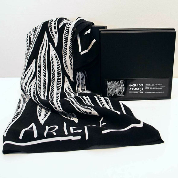 A Black and white silk scarf. The Prickly Wattle or Arlepe is depicted in white on the black background. The Text 'Arlepe' appears in white.