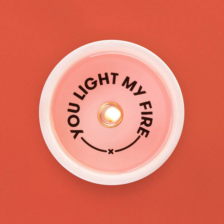 "A pink toned tealight candle in a ceramic holder. Shown alight, from above, displaying the secret message ""You light my fire"" which becomes visible as the candle burns."
