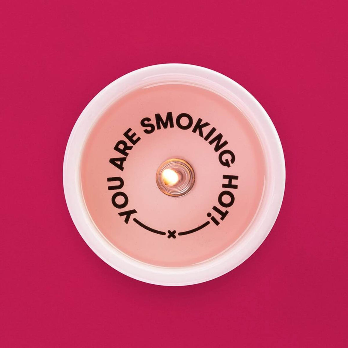 "A tealight candle in a ceramic holder. Shown alight, from above, displaying the secret message ""You are smoking hot"" which becomes visible as the candle burns."