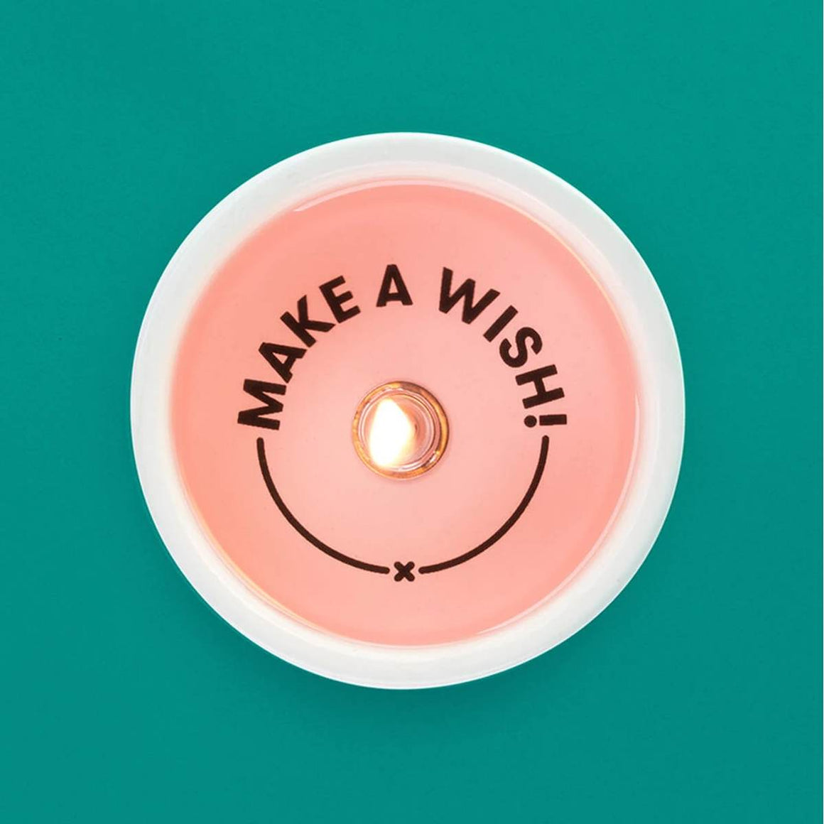 "A pink toned tealight candle in a ceramic holder. Shown alight, from above, displaying the secret message ""Make a Wish"" which becomes visible as the candle burns."