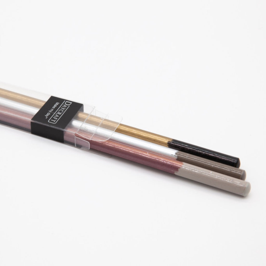 A set of three pencils featuring gold, silver and copper brushstroke design on each shaft.